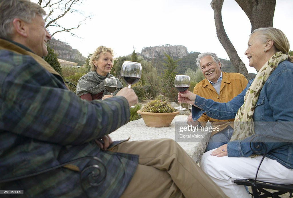 Four Senior Friends Sitting at a Table Toasting Glasses of Red Wine : Stock Photo