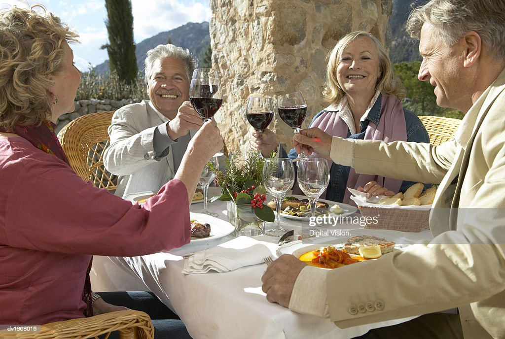 Four Senior Friends Sitting at an Outdoors Table Toasting Wine Glasses : Stock Photo