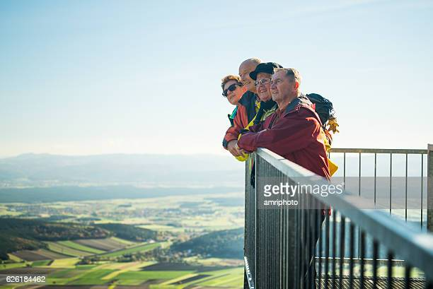 four senior hikers on viewpoint looking into distance - lookout tower stock pictures, royalty-free photos & images