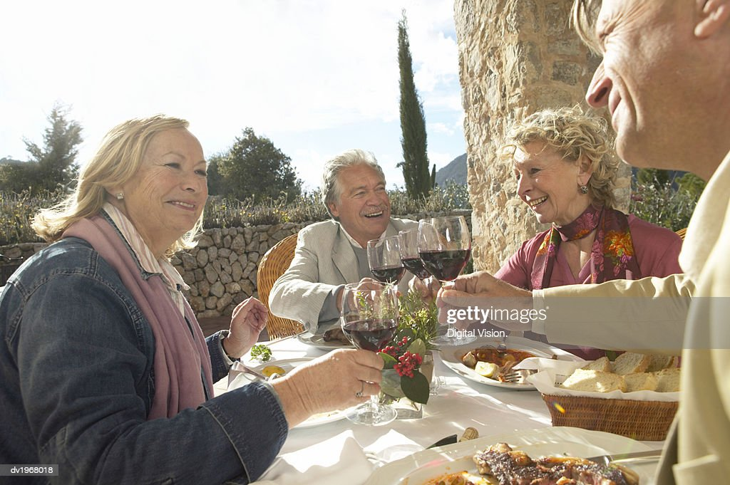 Four Senior Men and Women Sit at a Table on a Terrace Having Dinner and Making a Toast With Red Wine : Stock Photo
