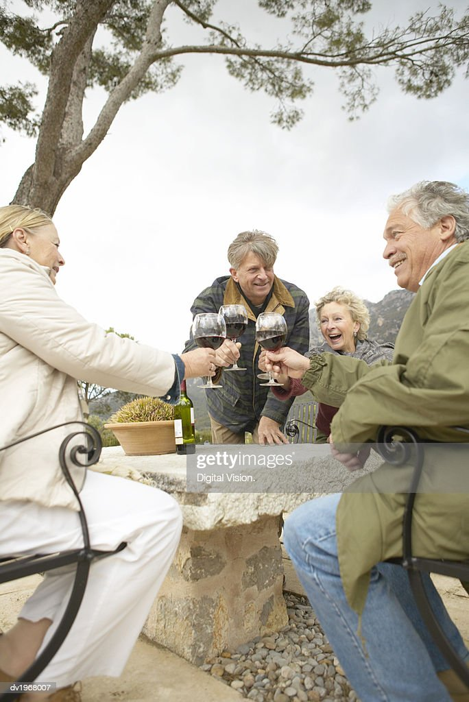 Four Senior Men and Women Sit at a Table on a Terrace Making a Toast With Glasses of Red Wine : Stock Photo