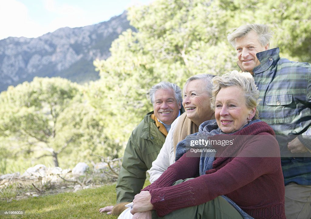 Four Senior Men and Women Sit in the Countryside, Looking at the View : Stock Photo