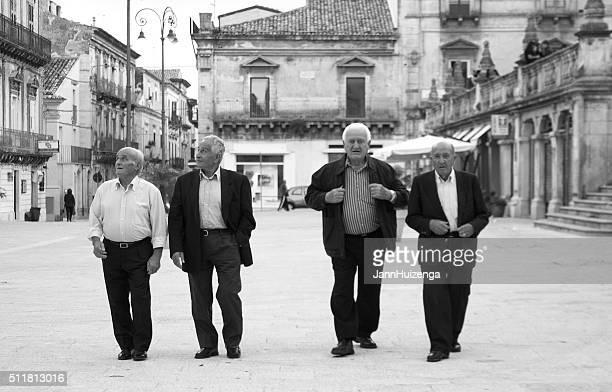 Four Senior Men Cross Piazza Duomo in Sicily, Italy