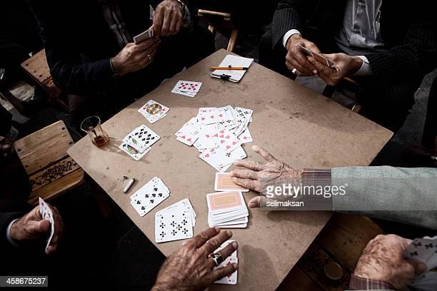 Cuatro hombres mayores jugando cartas
