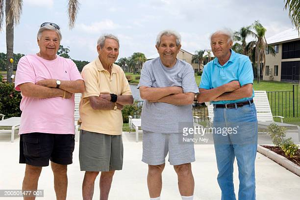 Four senior men with arms crossed over chests, portrait