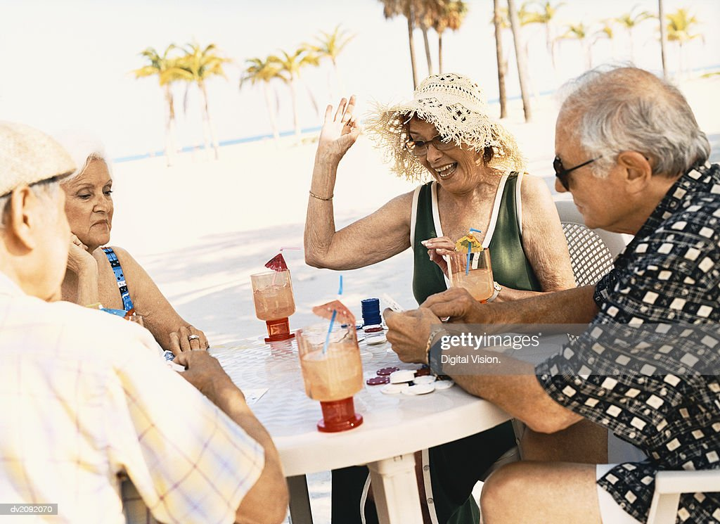 Four Senior People Playing Poker on the Beach : Stock Photo