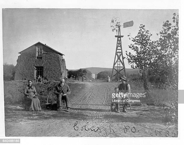 Four settlers gather in front of a sod house with a windmill in the distance | Location Coburgh Nebraska USA