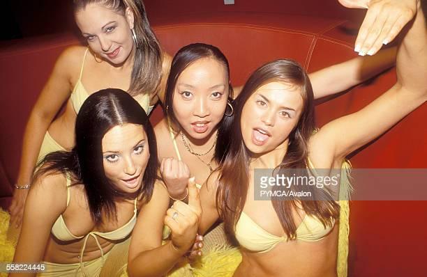 Four sexy girls with the same bikini gesturing to the camera UK 2005