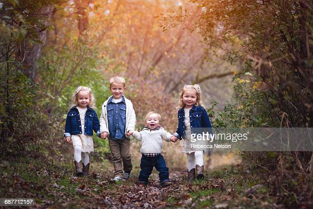 four siblings holding hands on forest path