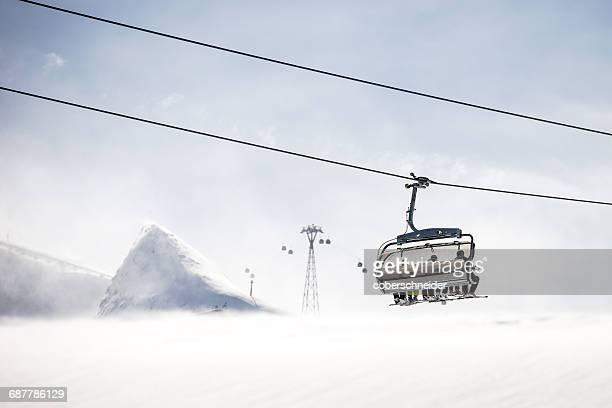 Four skiers sitting on a chairlift, Kitzsteinhorn, Salzburg, Austria