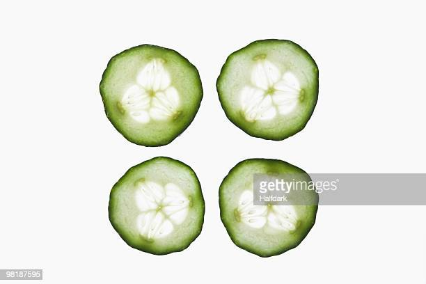 four slices of an organic cucumber on a lightbox - lightbox stock photos and pictures