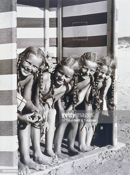 Four small girls in beach hut group portrait