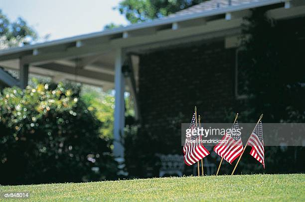 Four Small Stars and Stripes Flags Stuck in a Garden Lawn