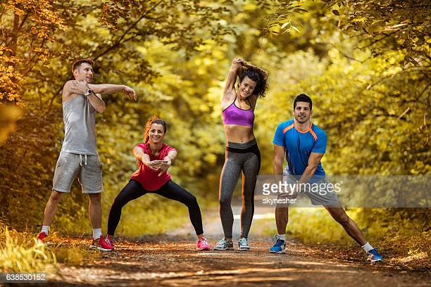 Four smiling athletes doing relaxation exercises at the park.
