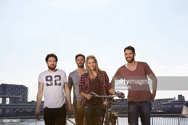 four smiling friends with bicycle - riverbank stock photos and pictures