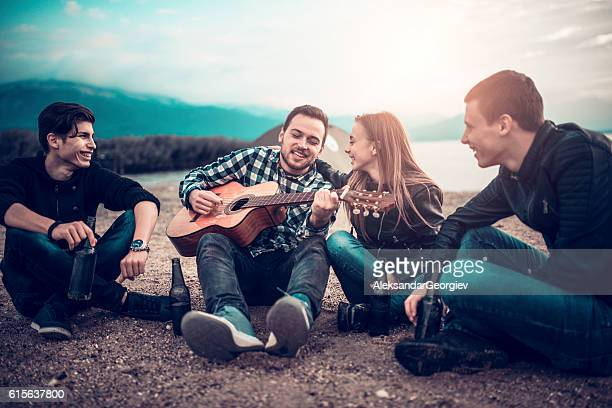 Four Smiling People with Acoustic Guitar Singing on Beach Camping