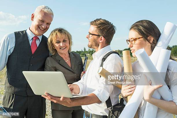 Four smiling people with laptop and construction plans