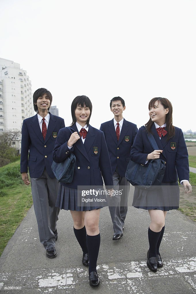 Four Smiling School Students Walking on a Path : Stock Photo