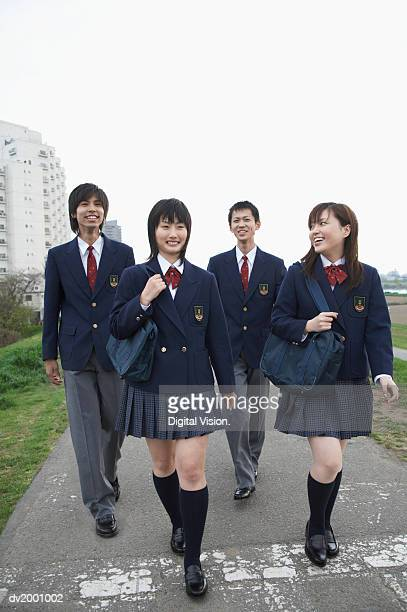 Four Smiling School Students Walking on a Path
