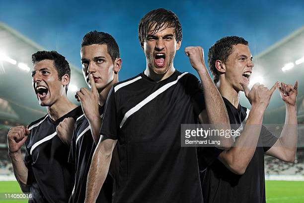 Four soccer players cheering, close up