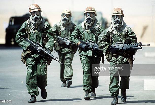 Four soldiers from the 82nd Airborne Division walk around their camp wearing protective masks in this undated photo from during Operation Desert...