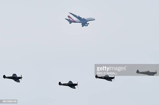 Four Spitfire aircraft fly beneath a long-haul passenger jet as they pass above aircraft at Biggin Hill airfield in Kent, on August 18, 2015. World...