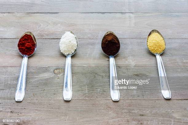 four spoons with various ingredients lying in row on wooden surface - couscous marocain photos et images de collection