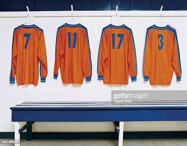 four sports strips hanging in a changing room - traje de fútbol fotografías e imágenes de stock