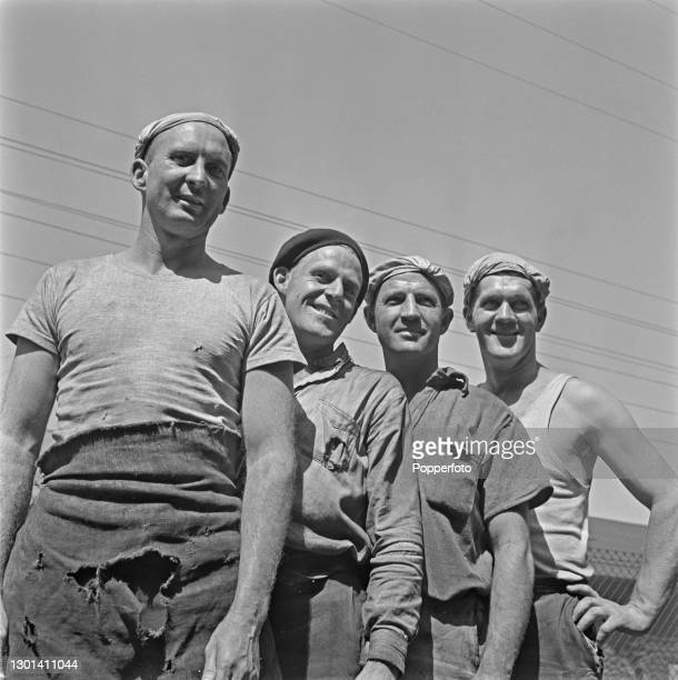 Four steelworkers pose in their workwear at the BHP steelworks on the waterfront in Newcastle, New South Wales, Australia in October 1948.