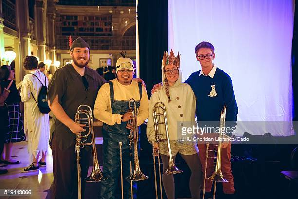 Four students all holding trombones dressed in costumes the leftmost male student dressed as Peter pan the male student second from the left dressed...