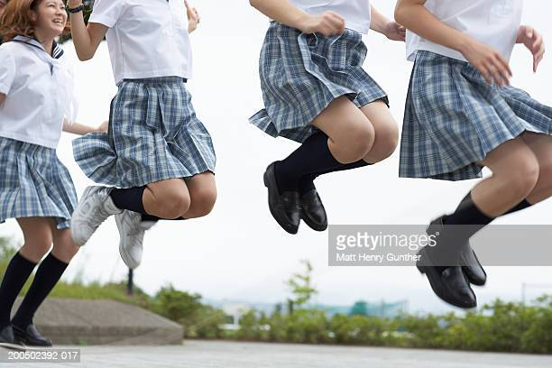 Four students (15-18) in school uniforms jumping in midair, side view