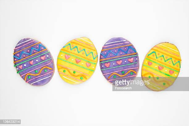 Four sugar cookies in shape of Easter eggs with decorative icing.