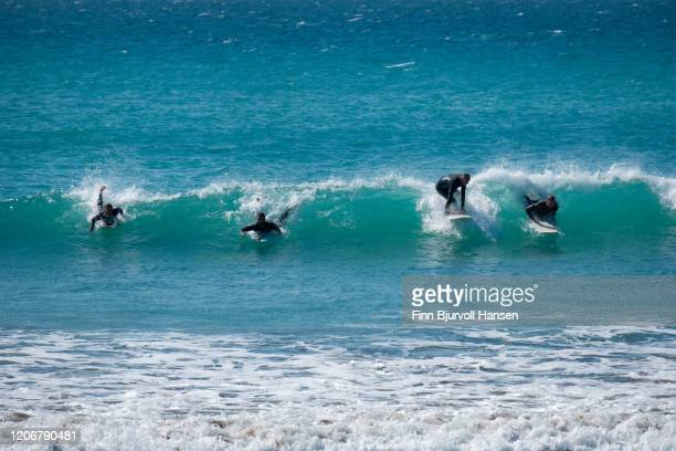four surfers catching a wave at the same time - finn bjurvoll stockfoto's en -beelden