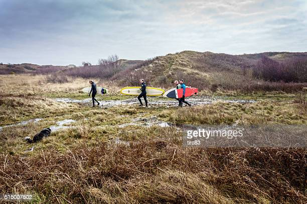 Four surfers walking through boggy countryside