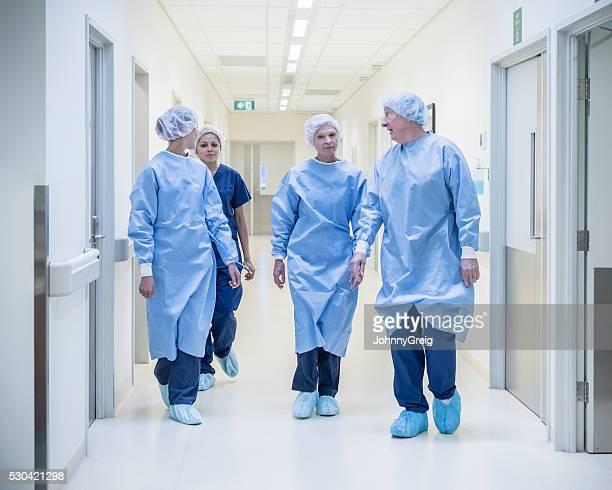 Four surgeons in hospital corridor wearing scrubs, walking toward camera
