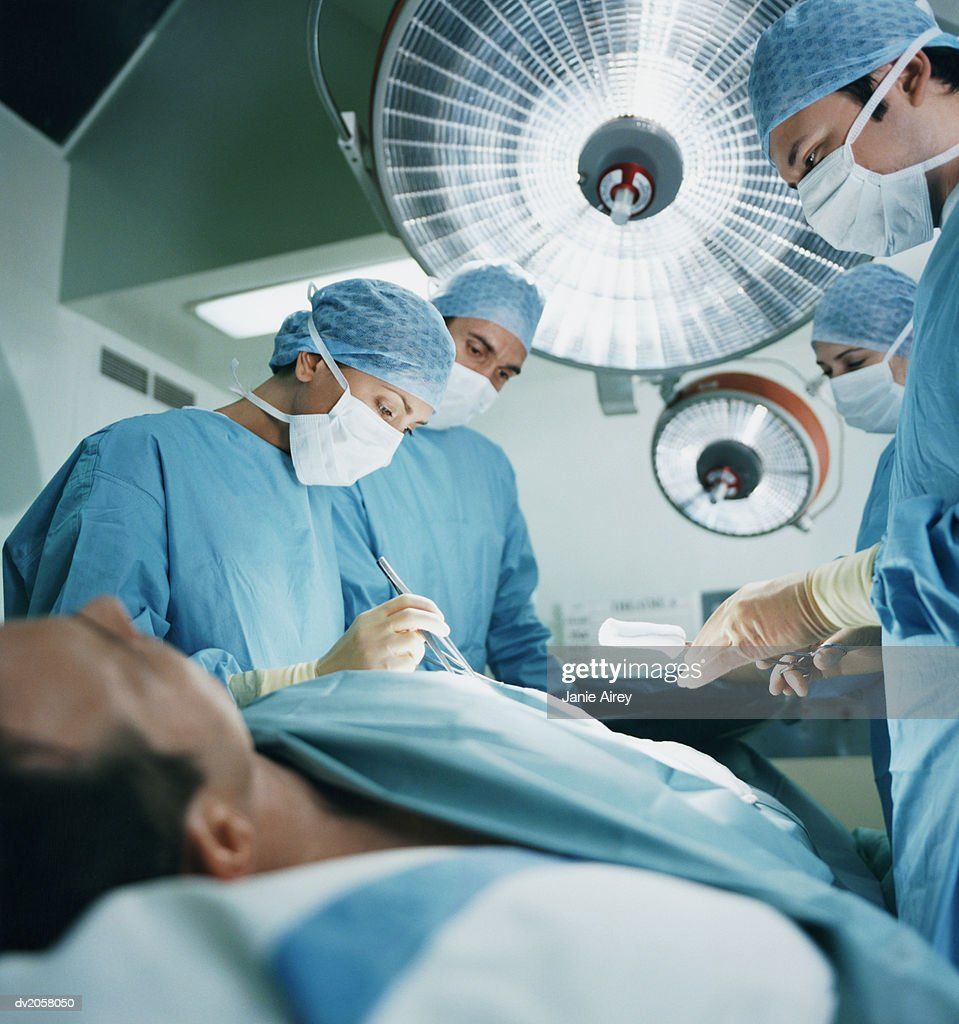 Four Surgeons Operating on a Patient : Stock Photo