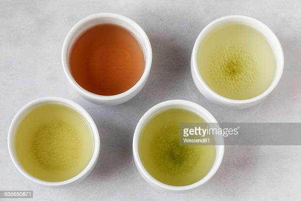 four tea bowls of sencha, gyukuro, hojicha und genmaicha - 温かいお茶 ストックフォトと画像