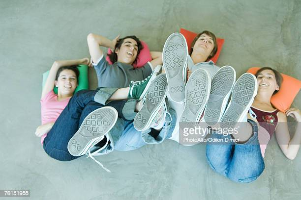 'Four teen friends lying on backs on floor, holding up legs, focus on soles of shoes'