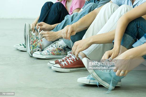 'Four teen friends tying laces, all wearing canvas shoes'