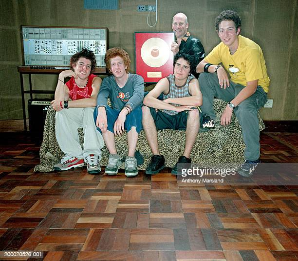 Four teenage boys (16-18) on sofa with man holding gold disc, portrait