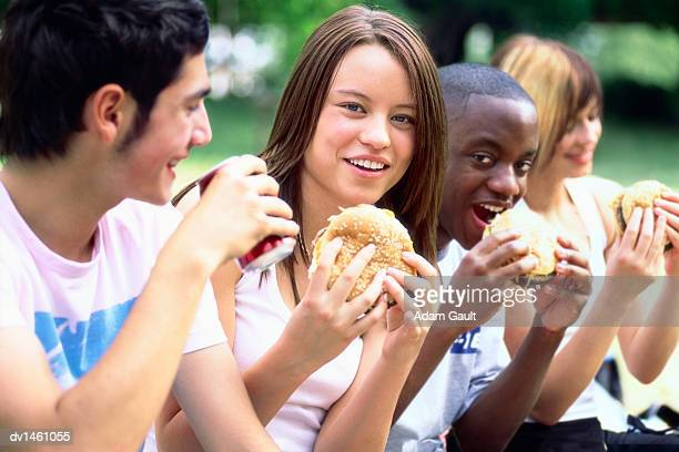 Four Teenage Friends Sit Side-by-Side Eating Fast Food in a Park