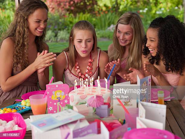 Four teenage girls at birthday party smiling outdoors