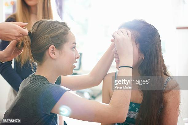 Four teenage girls doing each others hair and make up in bedroom