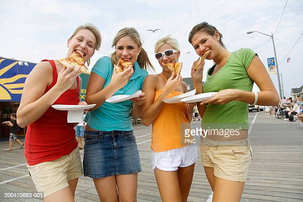 four teenage girls (16-18) eating pizza on boardwalk, portrait - ocean city new jersey stock pictures, royalty-free photos & images