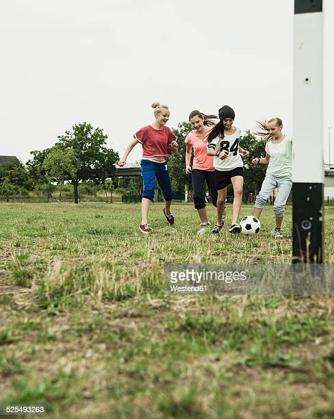 Four teenage girls playing soccer on a football ground