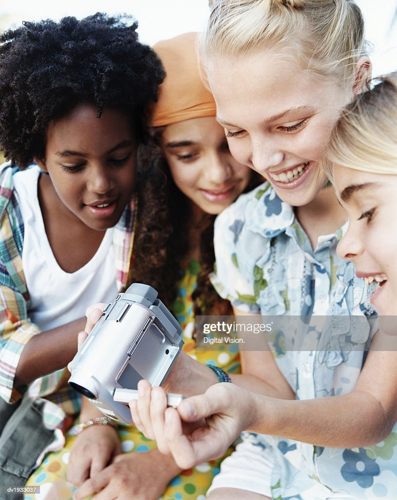 Four Teenage Girls Sitting Together and Looking Down at a Digital Camcorder : Stock Photo