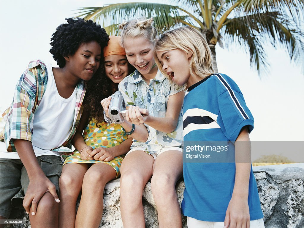 Four Teenage Girls Sitting Together on a Stone Wall and Looking Down at a Digital Camcorder : Stock Photo