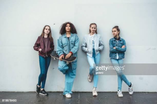 vier mädchen im teenageralter vor betonwand - jugendalter stock-fotos und bilder