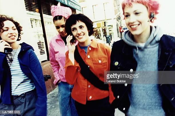 four teenage girls (15-17) using mobile phones (cross-processed) - alleen tienermeisjes stockfoto's en -beelden