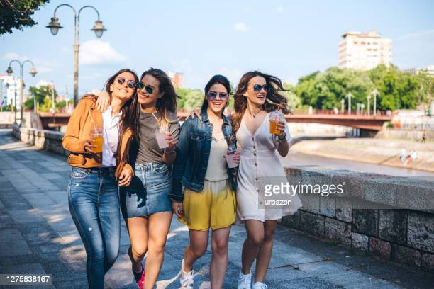 four teenage girls walking in a park - four people stock pictures, royalty-free photos & images